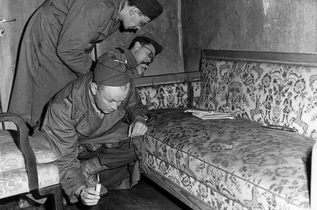 With only candles to light their way, war correspondents examine a couch stained with blood (see dark patch on the arm of the sofa) located inside Hitler's bunker, 1945. - See more at: http://www.clipouts.com/hitlers-bunker/#sthash.AbnwD8BW.dpuf