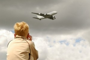 Small child deafened by roar of a large jet aircraft overhead