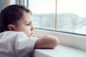 one sad little boy sitting near the window at the day time. Concept of sorrow.