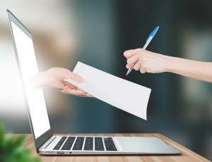 Firma del contratto, mano che esce da computer