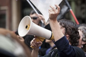 Unidentified young demostrator with megaphone and notebook protesting against austerity cuts