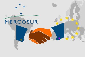 Trade agreement between Mercosur and the EU - On the maps of South America and Europe are the respective symbols. In front of it the illustration of a handshake as a symbol for a contract.
