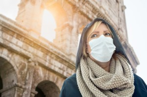Young Woman Wearing Face Mask Walks Near the The Roman Coliseum In Rome, Italy.