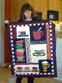 Terry S. holds up her coffee quilt.