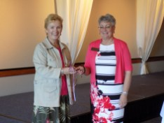 The gavel gets passed from outgoing president, Maxine Williams, to incoming president, Annette Godfrey.