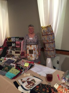 Maxine Williams modeling one her handmade aprons behind her table of handmade items.