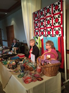 Dora Moore and Meridel Hedges display a beautiful array of quilted items.