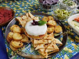 Layered Mediterranean torte with crostini and pita chips