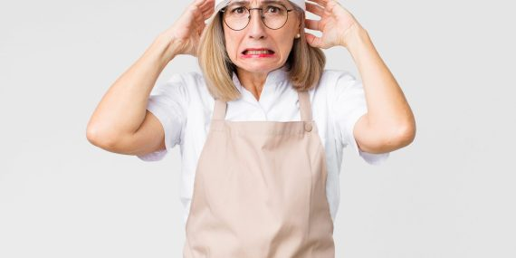 A woman with a chef hat and apron, looking very stressed. A metal pie pan is at the bottom left.