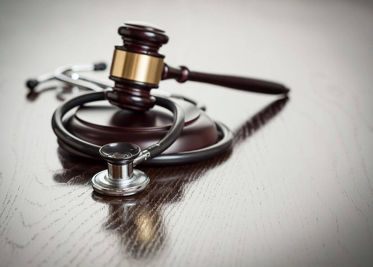 Gavel and stethoscope on reflective wooden table