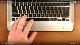 one hand rests on a Mac keyboard