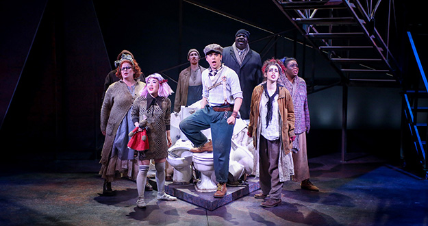 Mikko Juan (center) as Bobby Strong and the company of Urinetown (Photo Credit Jeff Carpenter)
