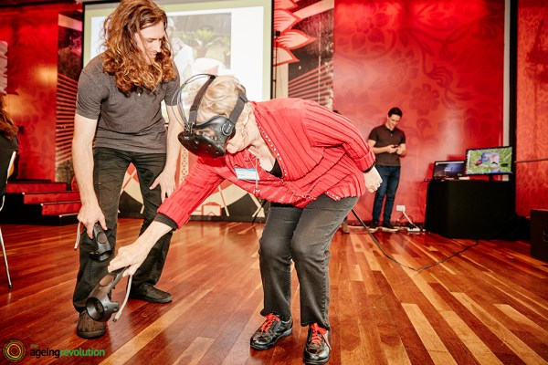 Brennan Facilitating an older women using VR Virtual Realityat the Age Tech VIvid Sydney Event hosted by The Ageing Revolution