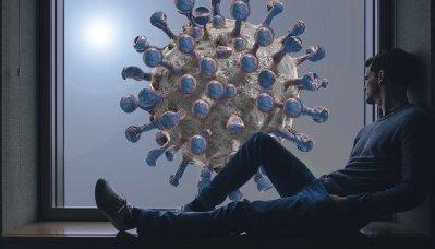 Mann sitzt am Fenster und starrt auf einen Covid-19 Virus