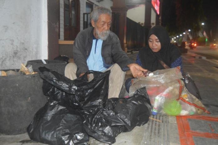 MEMILIH BARANG BEKAS. Soesilo Toer (kiri) saat memulung sampah ditemani wartawan Jawa Pos Radar Kudus, di Blora, baru-baru ini. Radar Kudus Photo