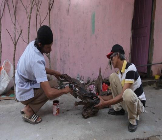 KREATIF. Japriansyah dan Adi pada saat mengolah batang pohon yang akan menjadi bahan dasar pembuatan pohon bunga hias, kemarin. Rizka Nanda-RK