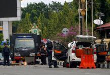 PERIKSA MOBIL. Tim Jibom Gegana Brimob Polda Riau memeriksa Avanza yang digunakan para terduga teroris yang berupaya menyerang Markas Polda Riau, Rabu (16/5). Defizal