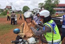 TEGUR. Polwan dari Sat Lantas Polres Kapuas Hulu mencontohkan pemasangan helm dengan benar kepada salah satu pengendara yang diberi teguran dalam Operasi Patuh Kapuas 2018, belum lama ini--Polisi for RK