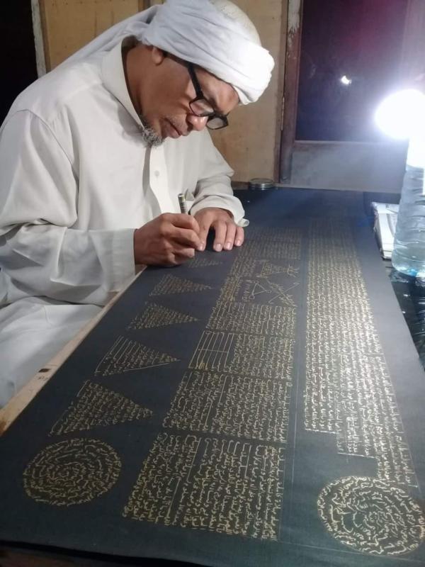 MENULIS AYAT ALQURAN. Usman Khalid sedang menyelesaikan rajah ayat suci Alquran di sebuah kertas di rumahnya, Desa Langko, Kecamatan Lingsar, Lobar. Lombok Pos Photo