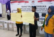 PROTES. Dua pendukung pasangan YAS membentengkan poster bertuliskan Pilkada ulang dan Pilkada cacat hukum di ruang rapat pleno, Jumat (6/7). Warga for RK
