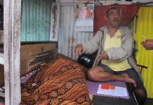 JENAZAH. Seorang warga duduk di samping jenazah Kaspin, lansia yang meninggal di kios milik Ismail, di Jalan Tanjungpura, Pontianak Selatan, Rabu (1/8)--Maulidi Murni.