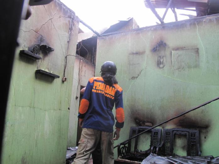 PUING. Petugas pemadam kebakaran tengah memastikan tidak ada lagi api di rumah Gang Serumpun II, Jalan Tabrani Ahmad, Kecamatan Pontianak Barat, Rabu (8/8) sore--Maulidi Murni