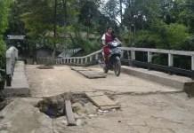 Jembatan Berlubang. Warga berkendara melalui jembatan Sungai Boli yang kondisi lantainya sudah berlubang serta mengancam keselamatan warga yang melintas. Warga for Rakyat Kalbar