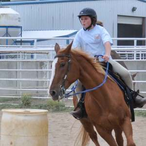 Advanced Wrangler Western Camp - Young woman riding horse around barrels.
