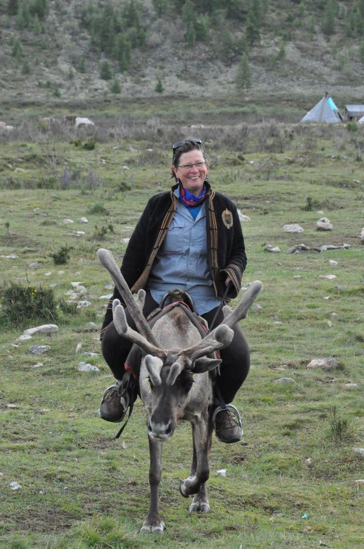 Julie Veloo is riding a reindeer in Mongolia.