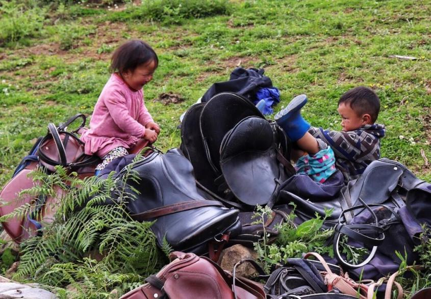A Bhutanese girl and boy play with saddles pretending to ride