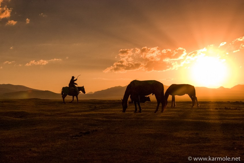 Sunset over the Mountains of Heaven in Kyrgyzstan with horses and a shepherd.