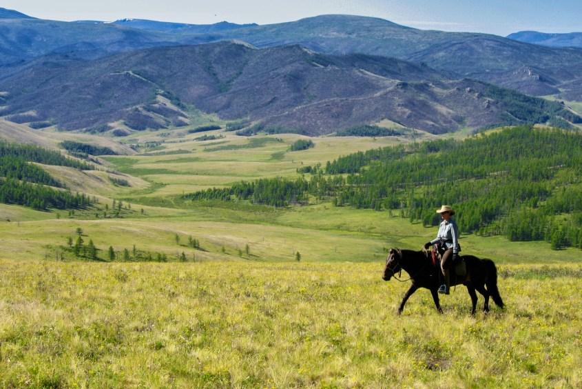 Horseback riding in beatiful scenery in Mongolia.