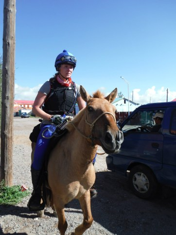 riding a horse into a mongolian soum during the mongol derby