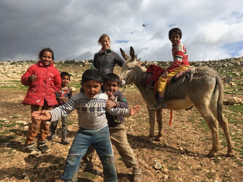 Bedouin kids hitching a ride on my donkey in Jordan