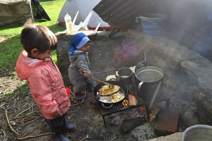 the kids help preparing breakfast during our trip through south america on horseback