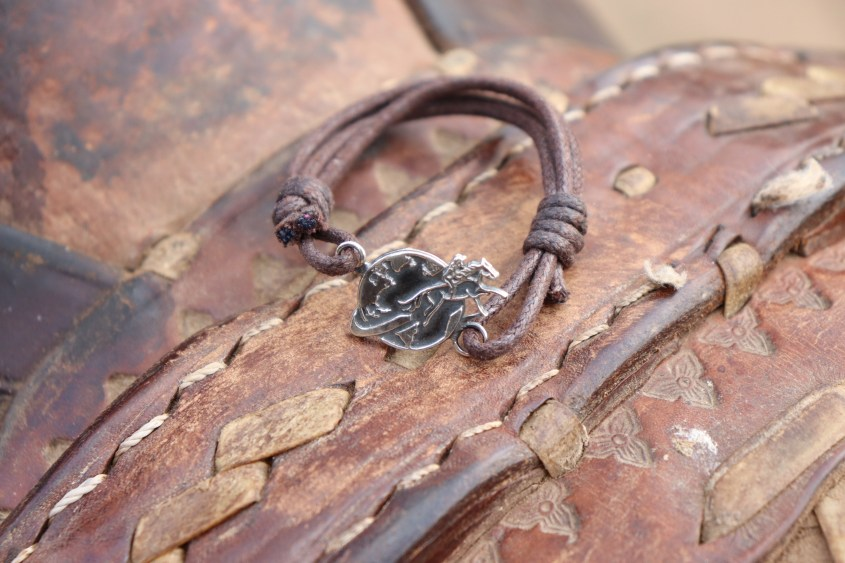 The Brown Equestrian Woman Bracelet presented on a leather saddle