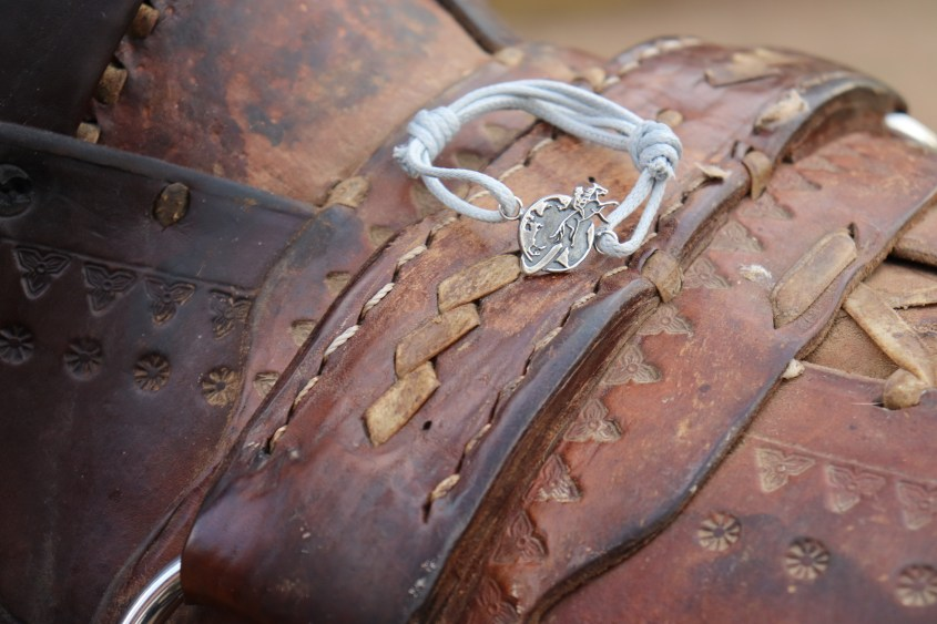 The Silver Bracelet shown on a rustic saddle
