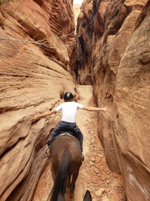 Riding on horseback through a narrow slot canyon in Utha, USA