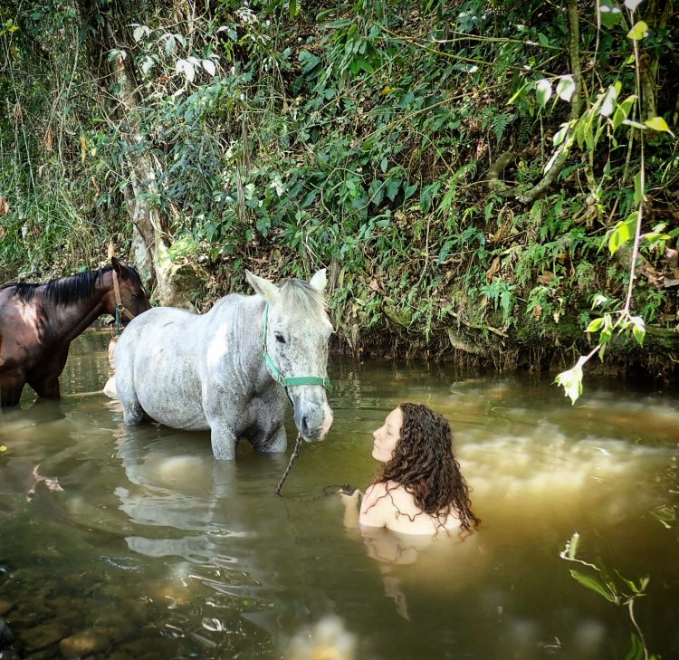 Escaping the midday heat with the horses by having a bath in a river togehter