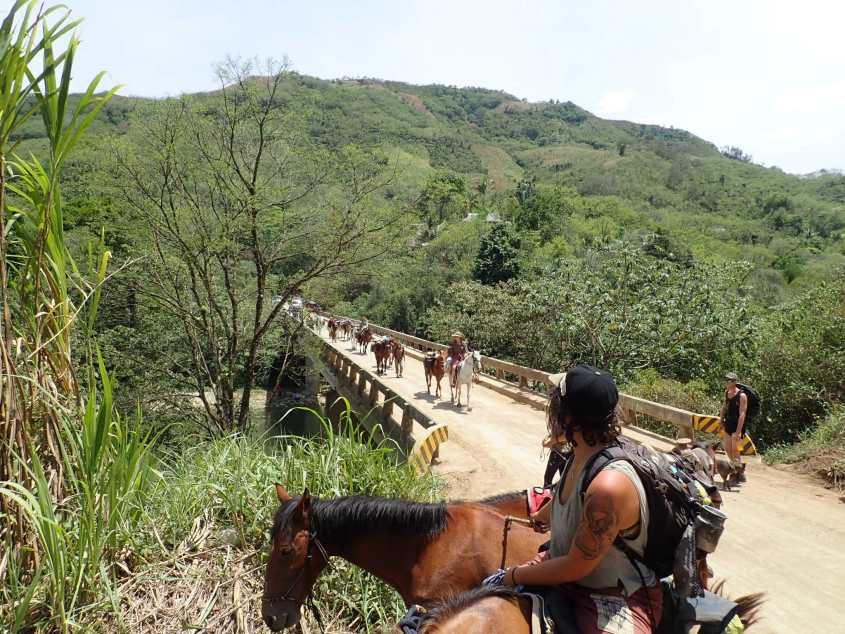 The horse caravan in crossing a bridge over the Cahabon river in Guatemala