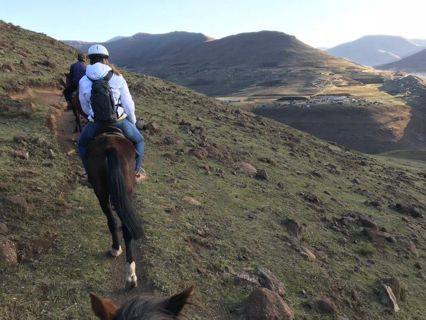 The group riding their horses along a mountain in Lesotho during a horse trekking adventure