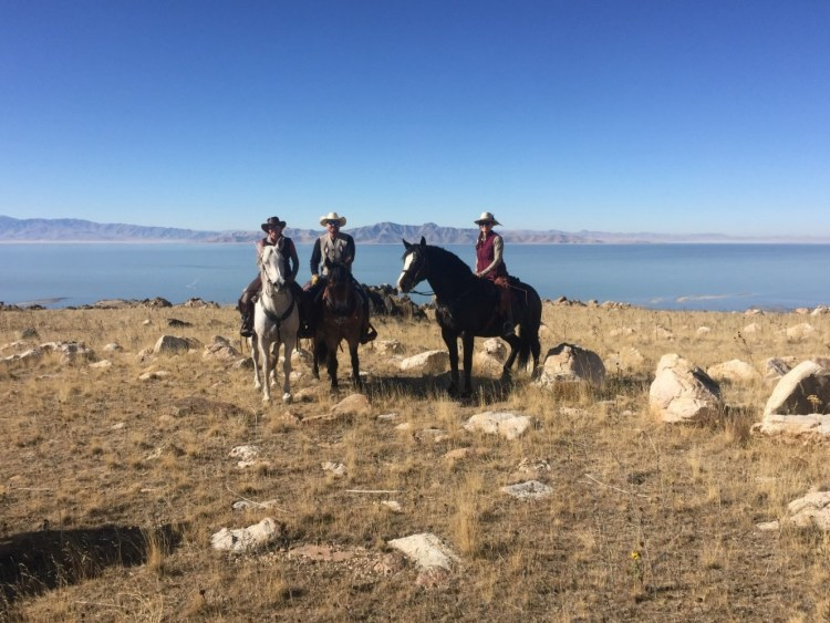 An adventuress and her friends posing during horse riding in Utah. They participate in the Bison Roundup on Antelope Island