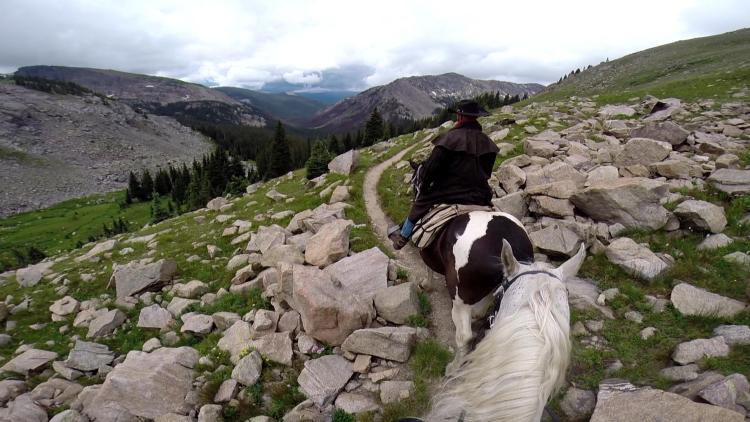 The horseback riding guide leads through a boulder field in the Rocky Mountains on the Continental Divide Trail in Colorado