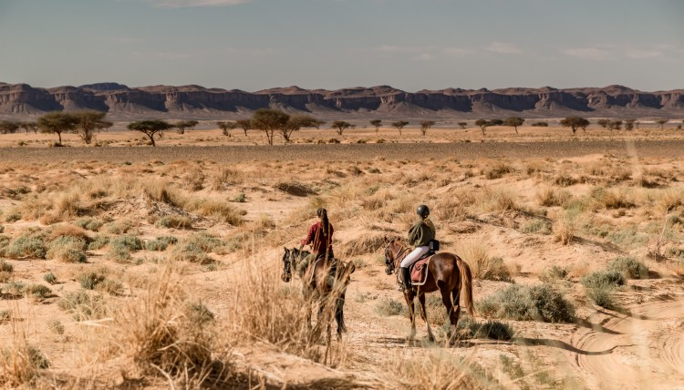 Two horse riders are overlooking the mountain rage Jbel Bani in Morocco
