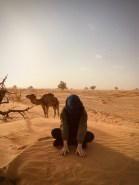 A women covering her face to protect it from a sand storm with a camel in the background