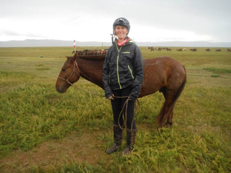 Krystal standing beside her horse after arriving at one of the horse stations during a Mongolian horse race