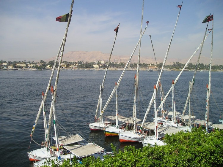 A couple of sail boats are floating in the Nile river next to a pier