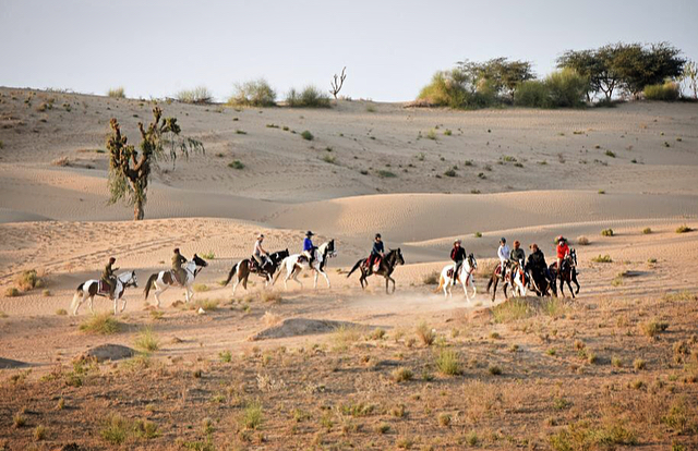 Horse riding through the desert dunes of Rajasthan in India