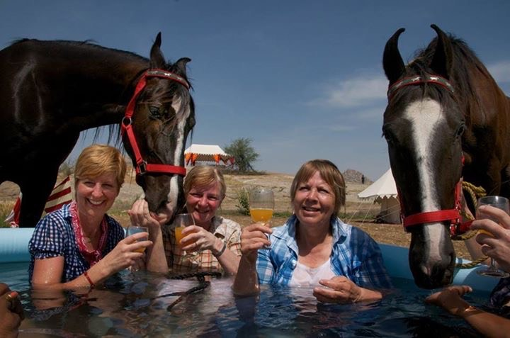 The group of travelers cools down in an inflatable pool with a drink during their horse riding trip in India