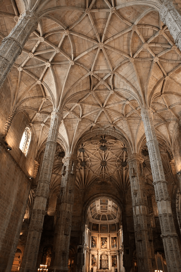 The inside of a Portuguese monastery with tall columns and arches